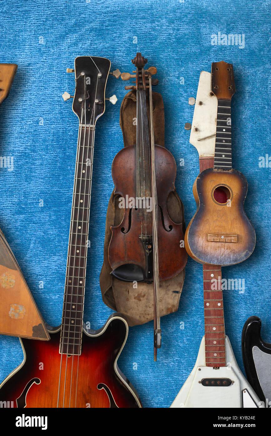 Musical instrument - Vintage bass guitar, acoustic, violin, balalaika on a blue plush background. - Stock Image
