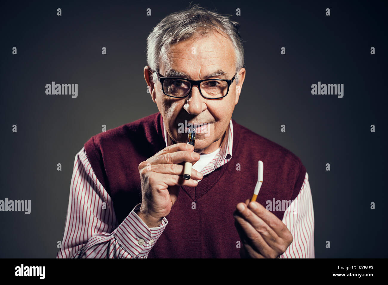 Portrait of senior man who is decided to quit smoking cigarettes in favor of electronic cigarette. - Stock Image