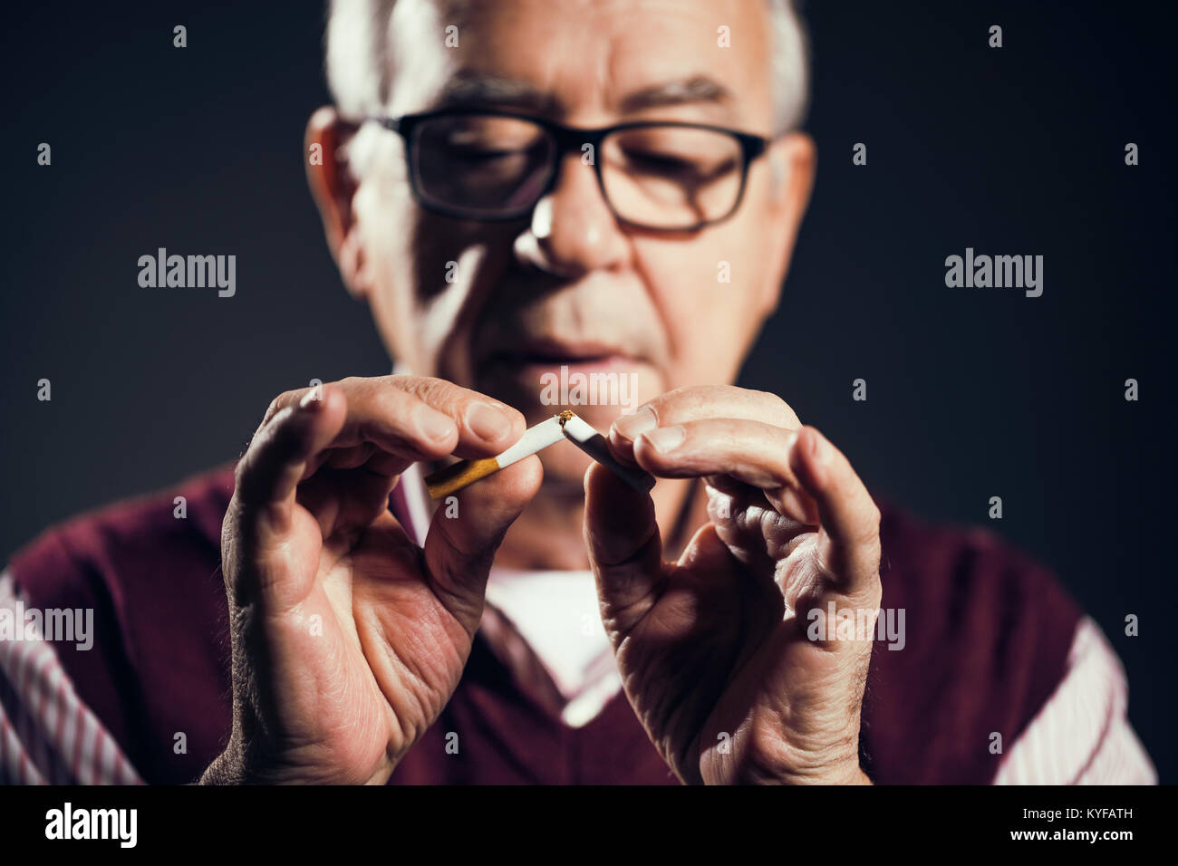 Close up image of senior man who is decided to quit smoking. - Stock Image