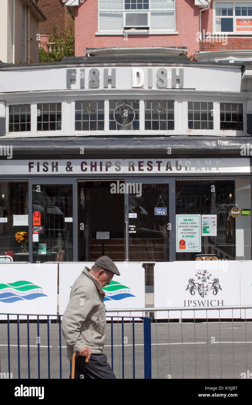 Senior citizen passes a Felixstowe fish and chip restaurant - Stock Image