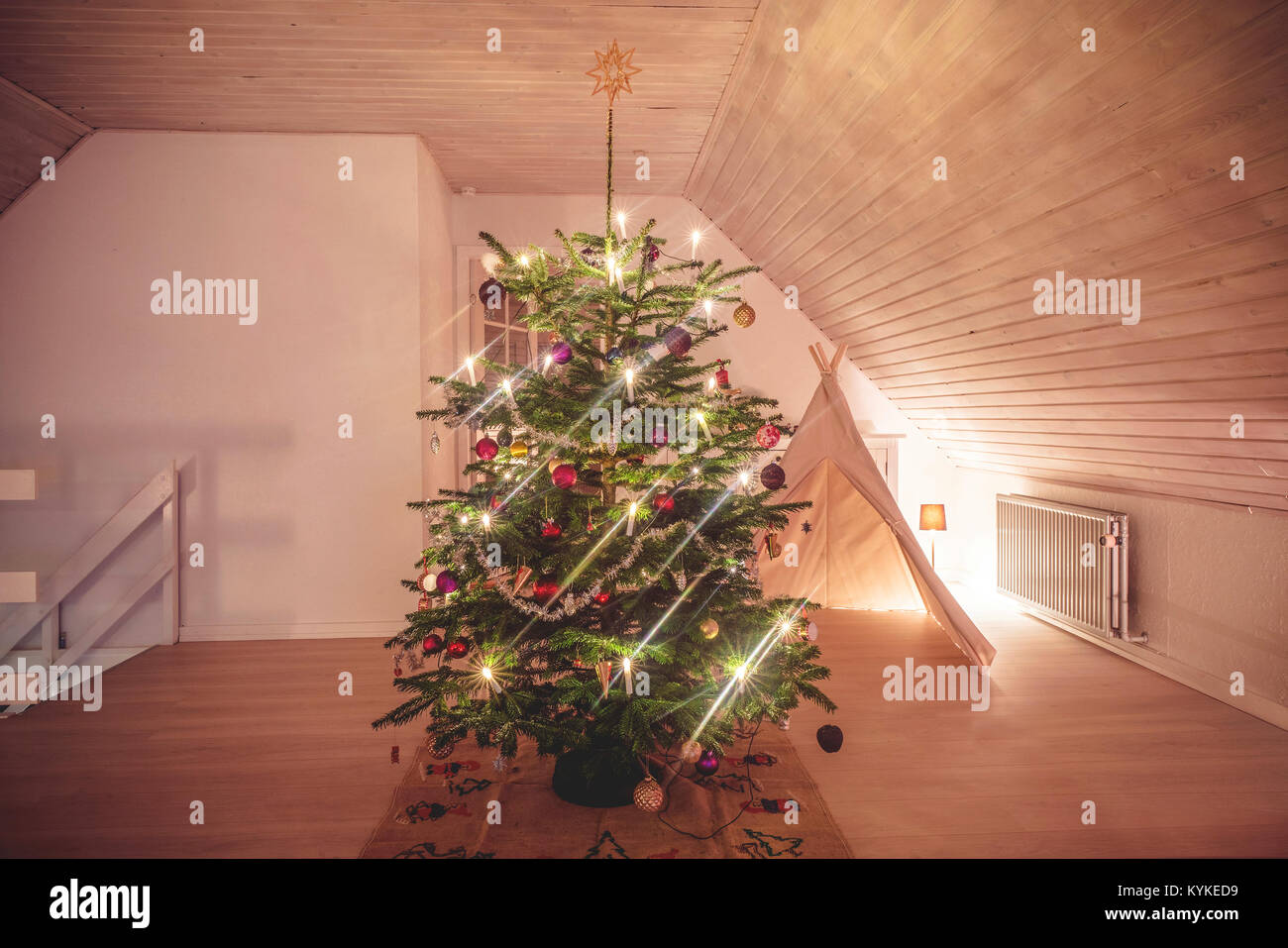 Christmas tree with glittering lights in a living room in the holidays decorated with baubles and a tent in the - Stock Image