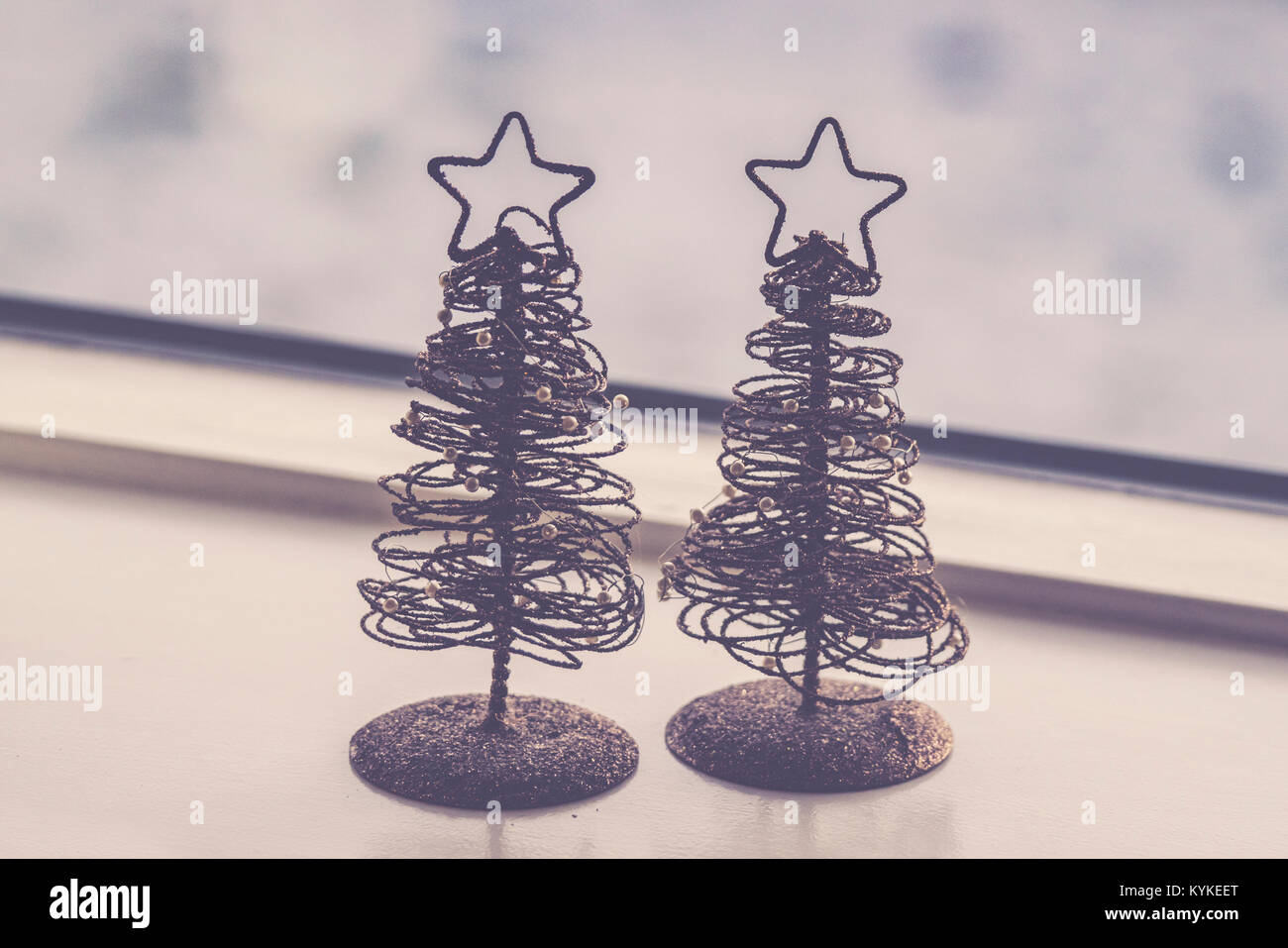 Two small decorative Christmas trees with glitter and stars in an ornament at Xmas - Stock Image