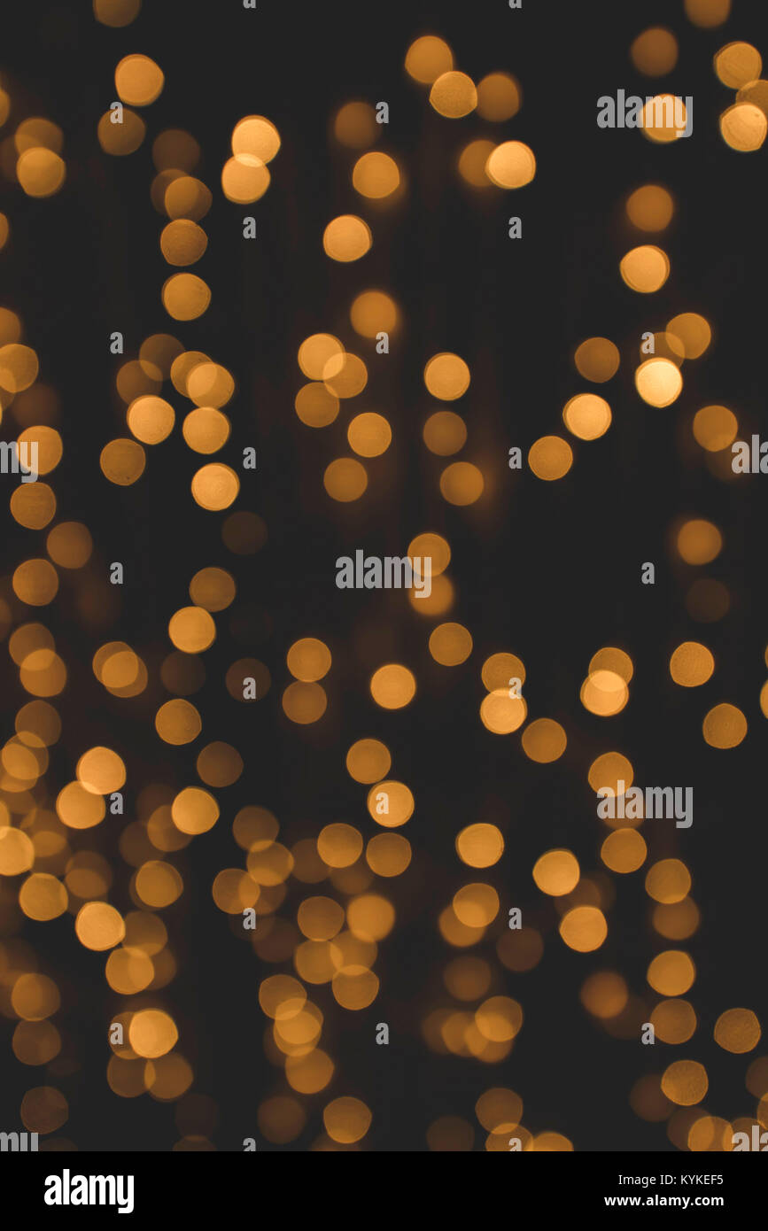 Bokeh light with glittering golden flares on a dark background with a matte effect - Stock Image