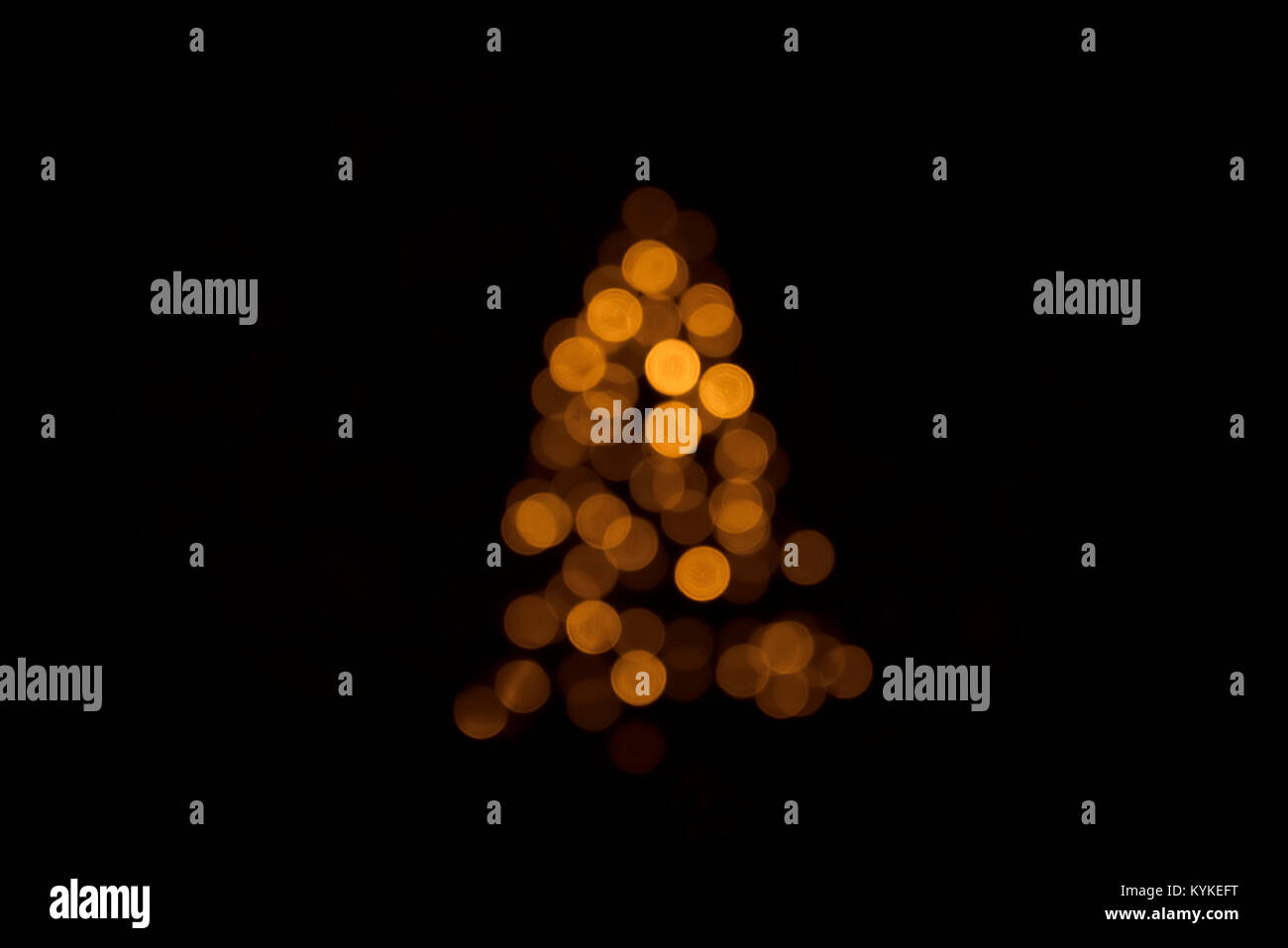 Bokeh lights on a Christmas tree with shining golden flares on a dark background - Stock Image