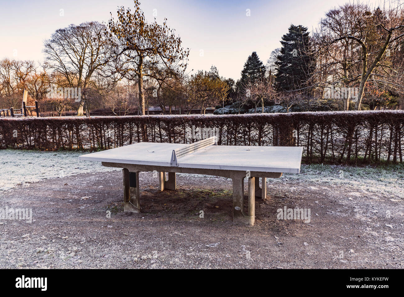 Outdoor table tennis made of concrete standing in a park in the winter - Stock Image