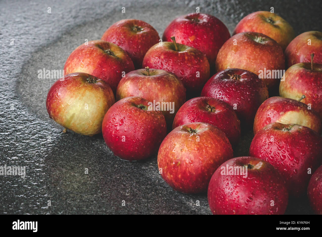 Wet apples on a granite rock in the rain in the fall in red colors with droplets - Stock Image
