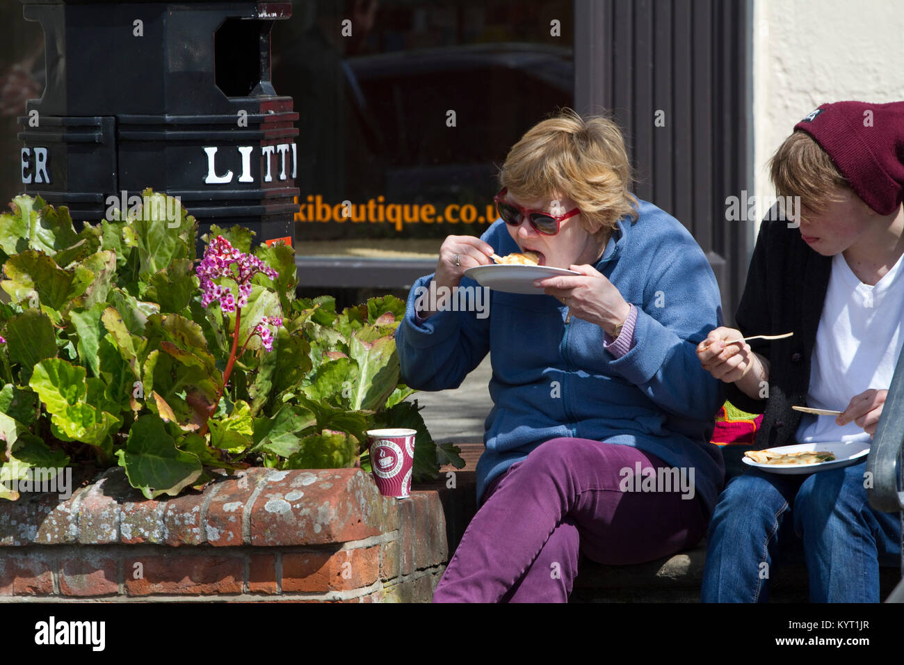 A couple outdoors sit on steps eating pancakes from paper plates - Stock Image