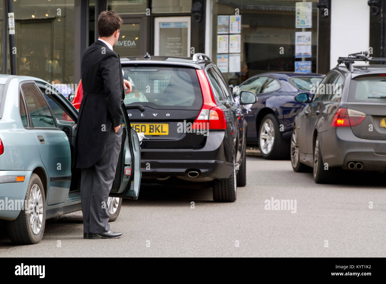 Man in a tail coat for a wedding stands by an open car door - Stock Image