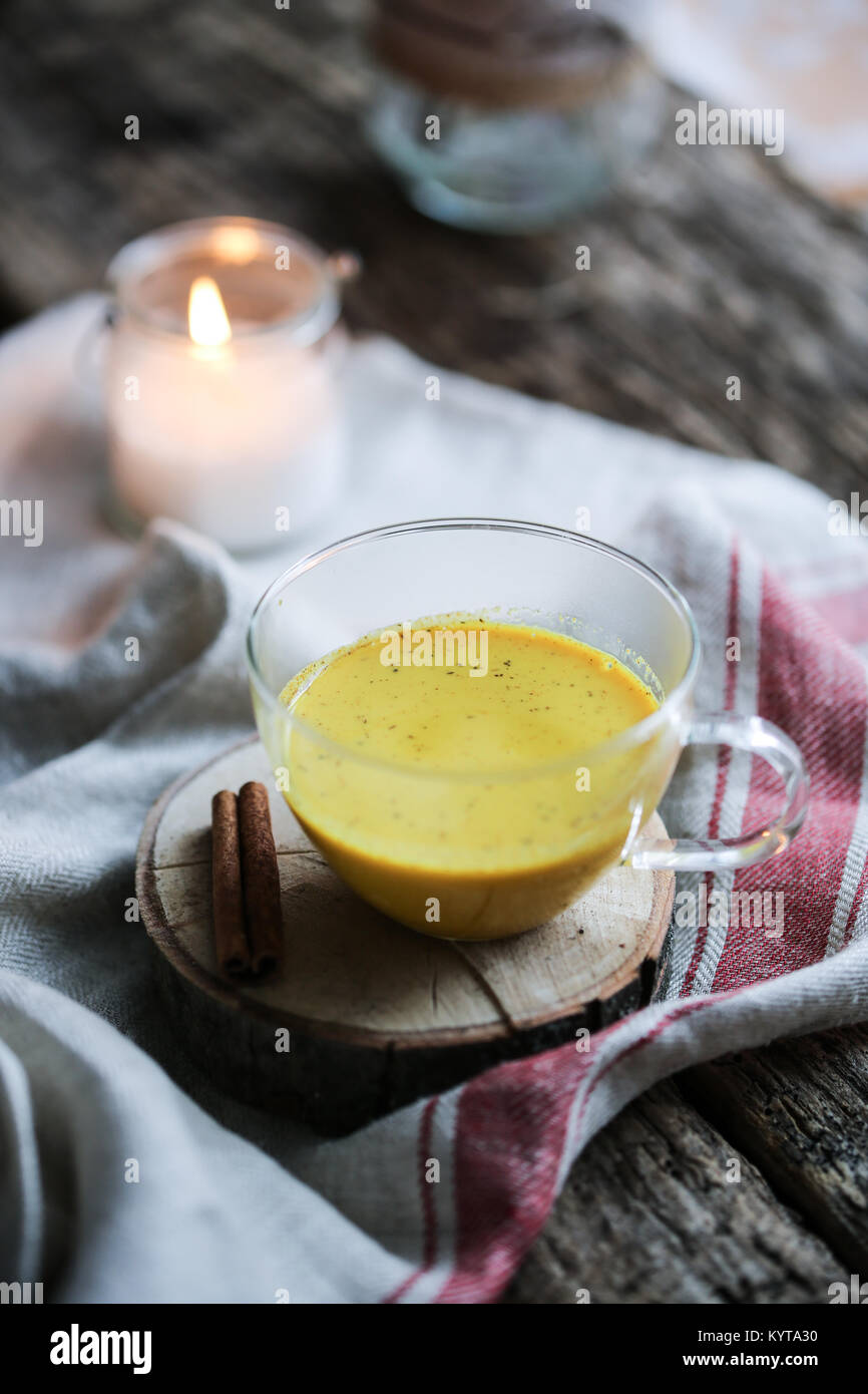 Bolstering Immunity with a cup of golden milk. Cup of golden milk on a table. - Stock Image