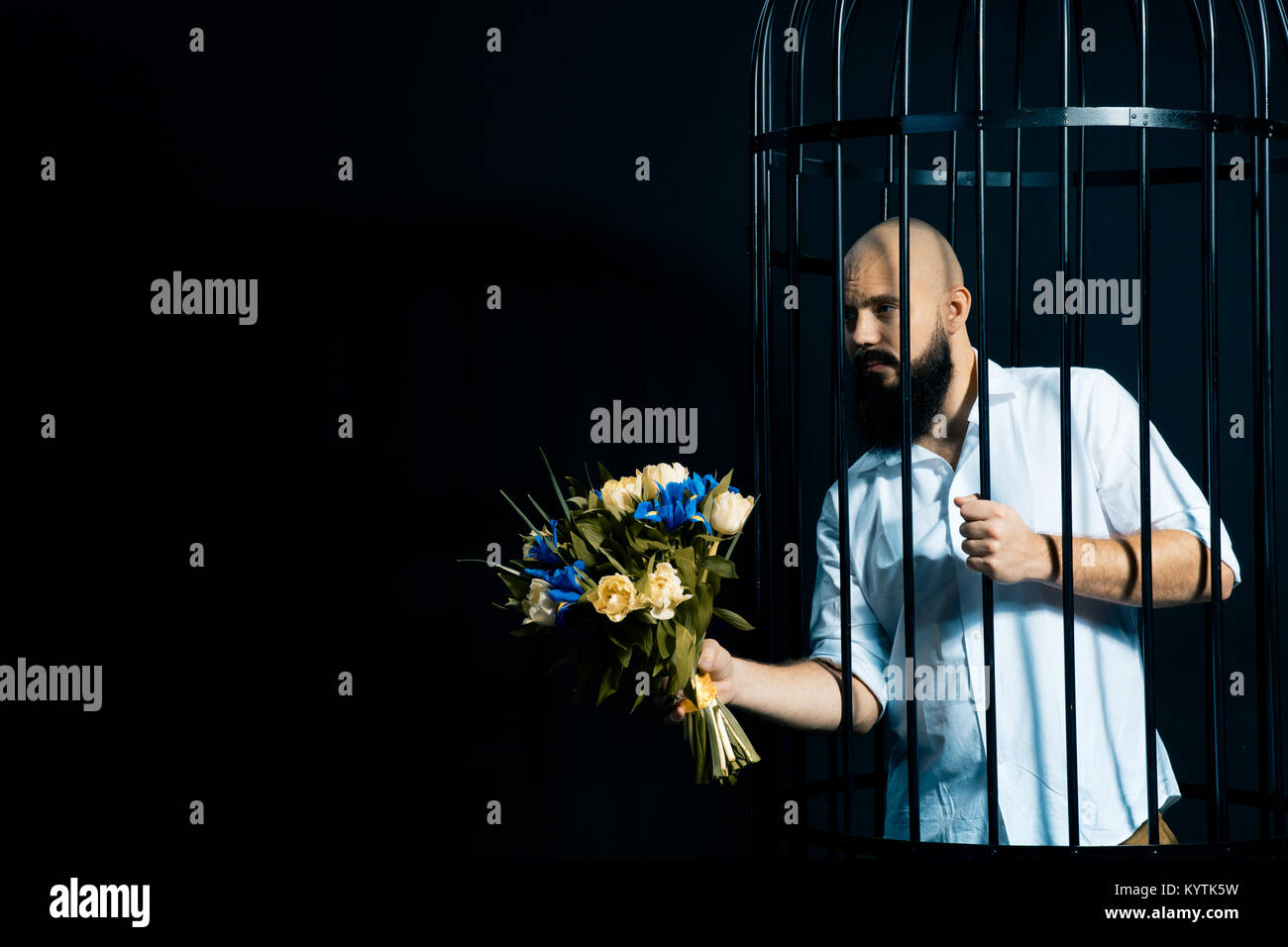 bearded man holding out a bouquet with flowers. The brutal man in the cage over black background. Stodio shot. Space - Stock Image