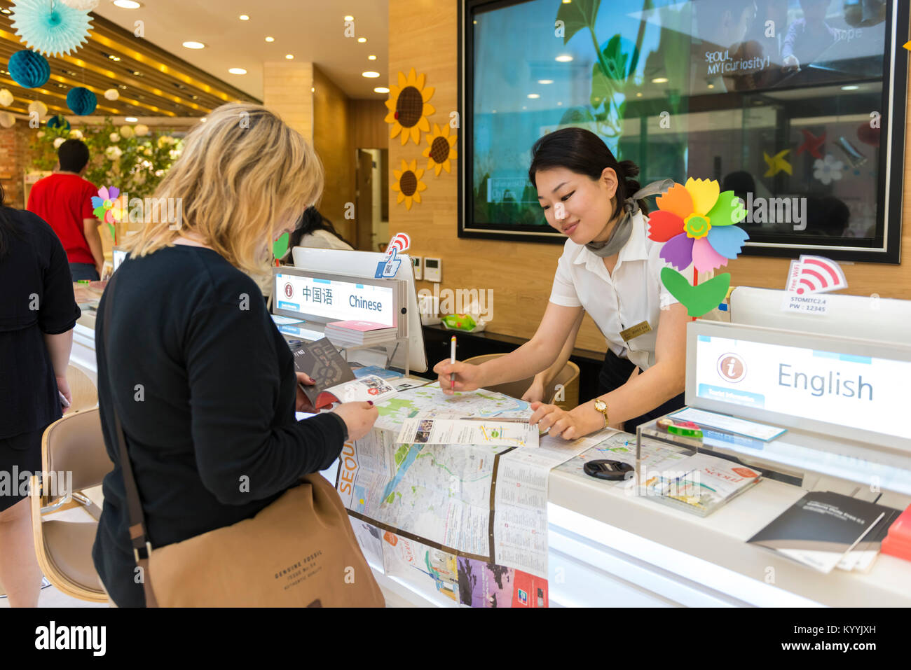 Tourist Office, Seoul, South Korea - woman tourist at the counter inside the tourism office asking for directions - Stock Image