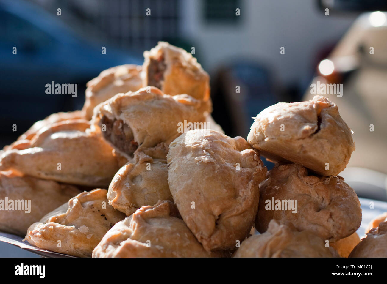 Piled up Cornish pasties on s street market stall - Stock Image