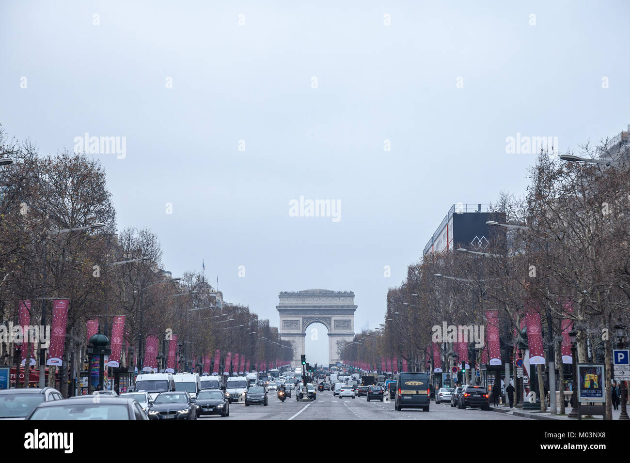 PARIS, FRANCE - DECEMBER 20, 2017: Champs Elysees avenue with the Arc de Triomphe in background during a cloudy - Stock Image