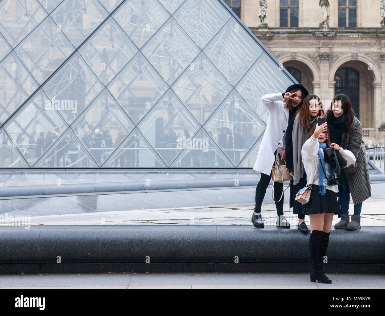 PARIS, FRANCE - DECEMBER 20, 2017: Chinese tourists taking selfie photos in front of the Louvre Pyramid. Louvre - Stock Image