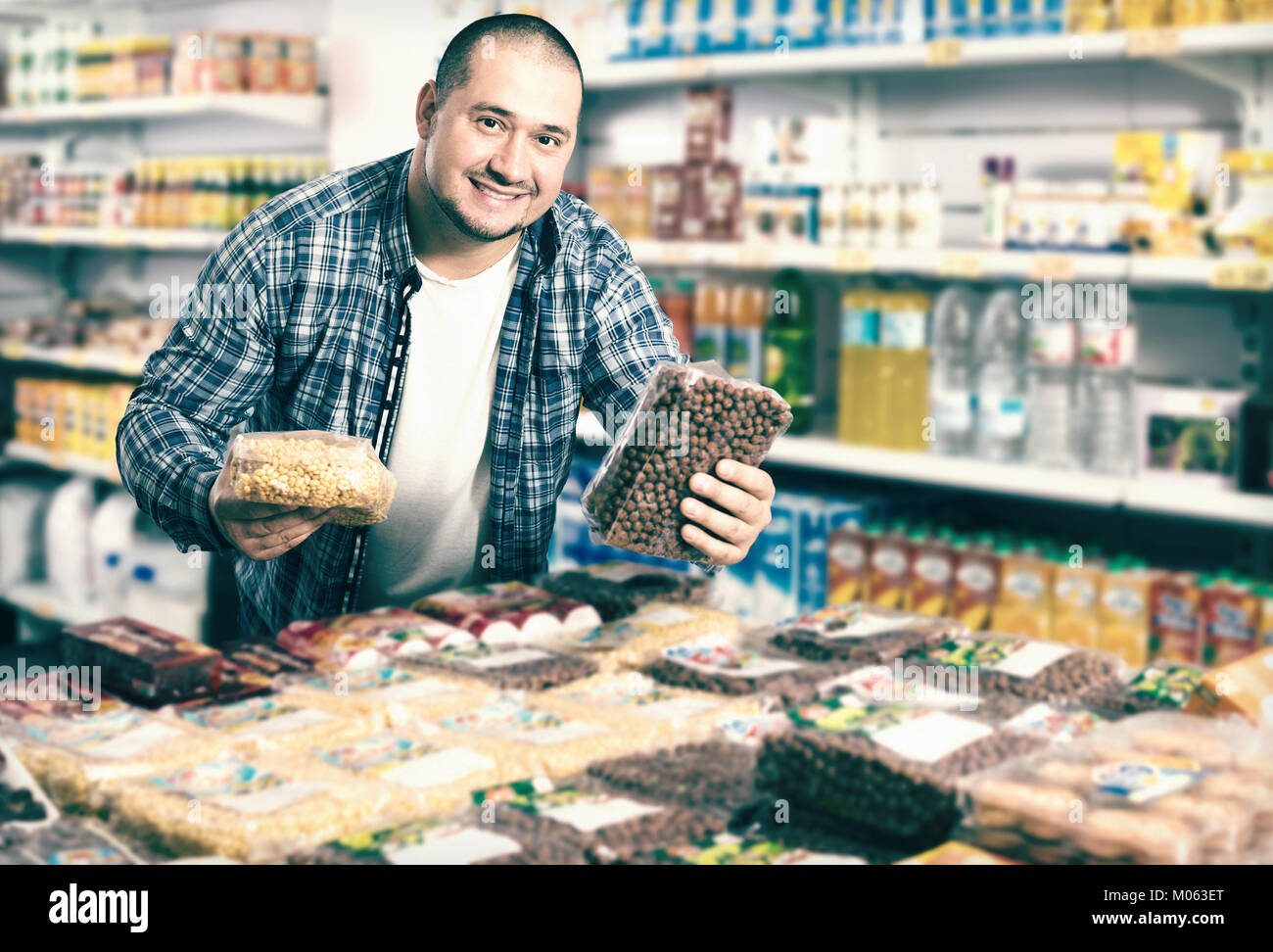 Smiling male purchaser buying kidney beans in local supermarket - Stock Image