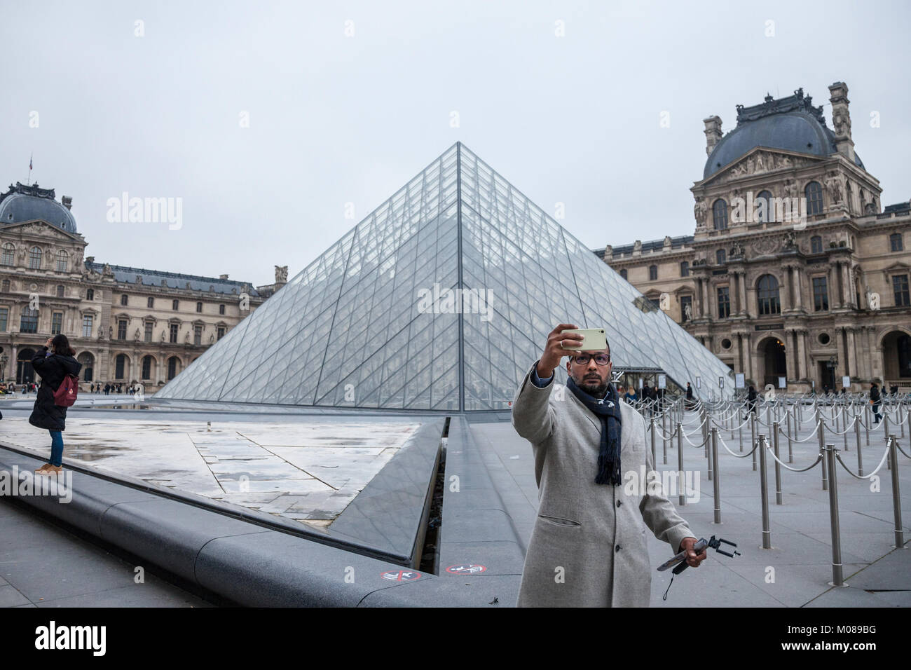 PARIS, FRANCE - DECEMBER 20, 2017: Tourist taking a selfie portrait in front of the Louvre Pyramid. Louvre pyramid - Stock Image