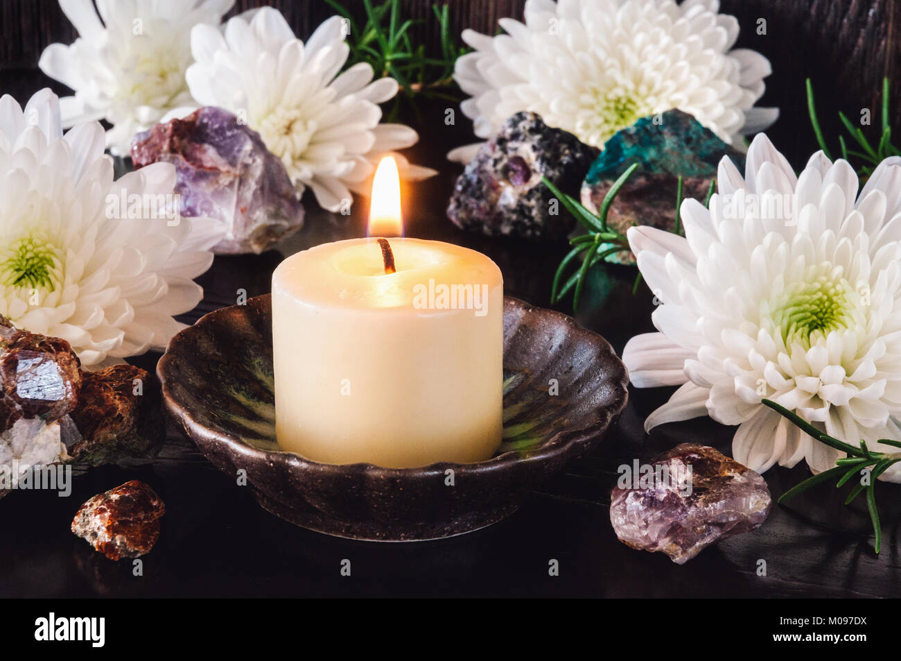 White Candle with White Chrysanthemum Flowers and Garnet, Amethyst, Ruby and Turquoise. - Stock Image
