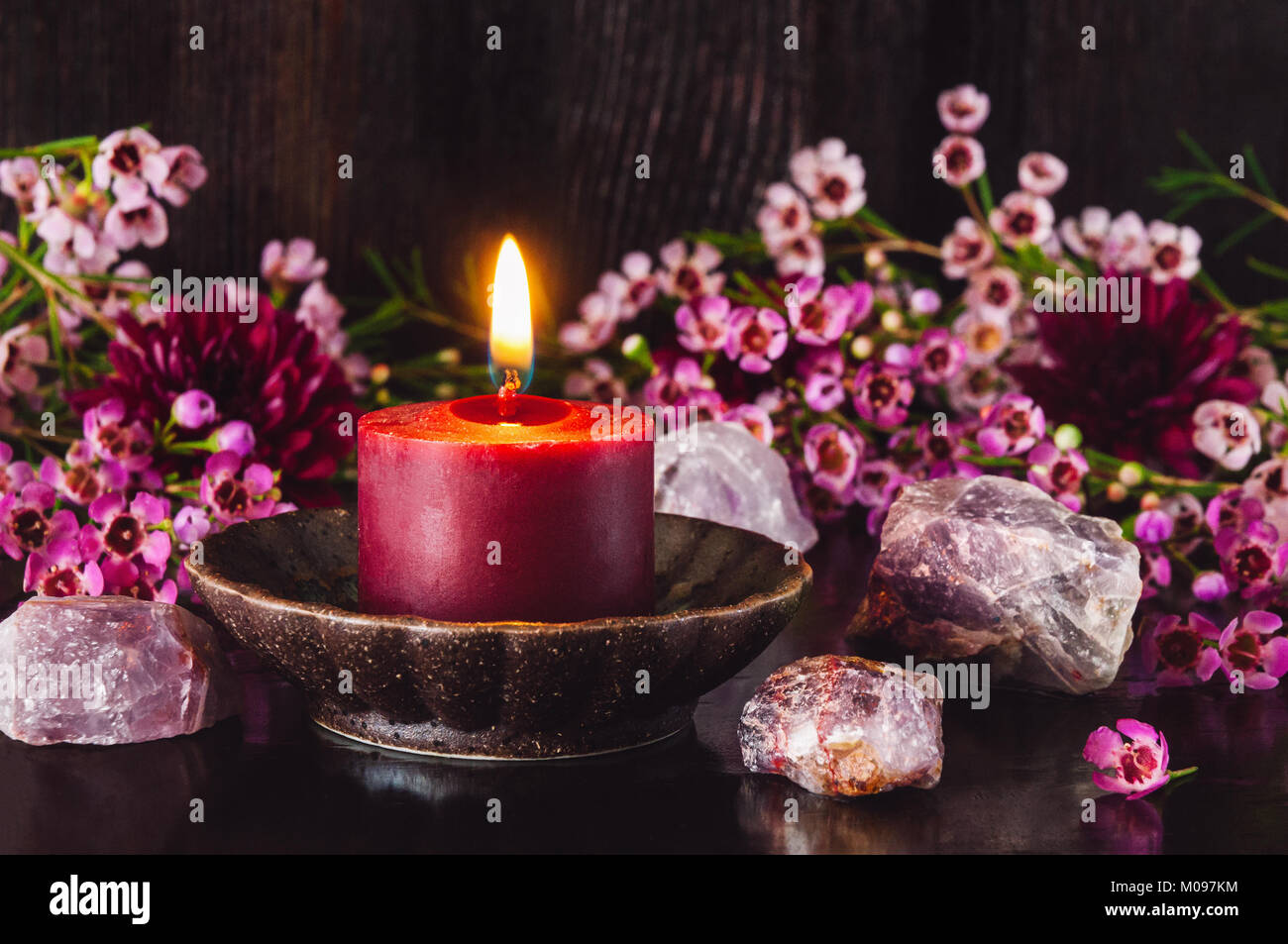 Red Candle with Amethyst Crystals and Mixed Flowers - Stock Image