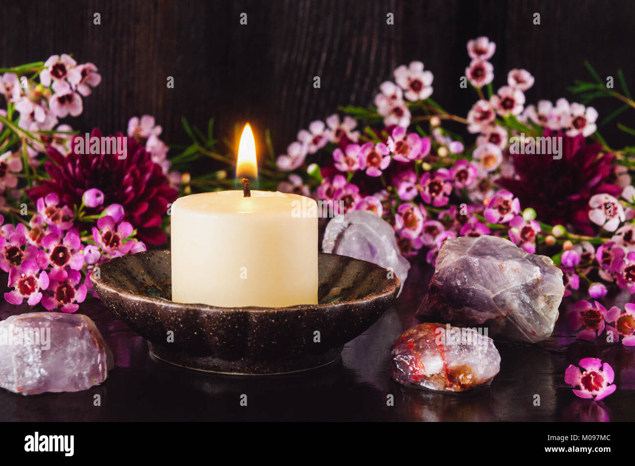 White Candle with Amethyst Crystals and Mixed Flowers - Stock Image