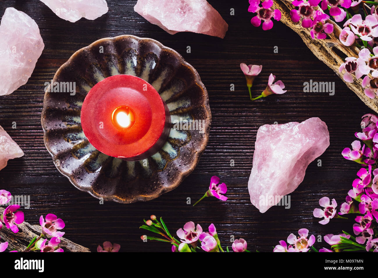 Red Candle and Rose Quartz with Flowers on Dark Table - Stock Image
