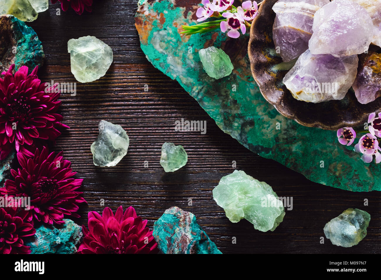 Rough Amethyst, Fluorite and Turquoise with Mixed Flowers on Dark Table - Stock Image