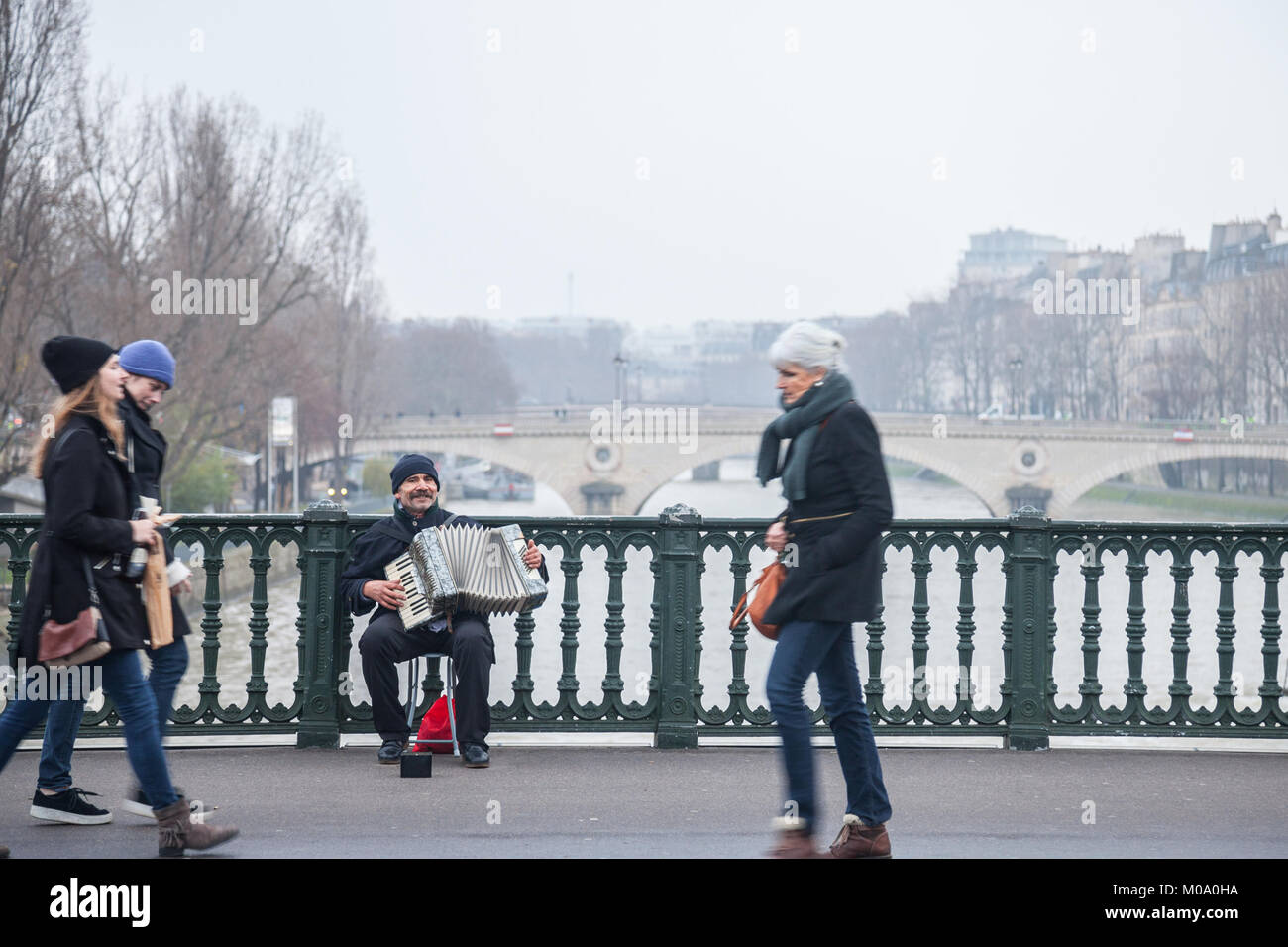 PARIS, FRANCE - DECEMBER 20, 2017:  Accordionist plating accordion on the Arcole bridge in Paris, over the Seine - Stock Image