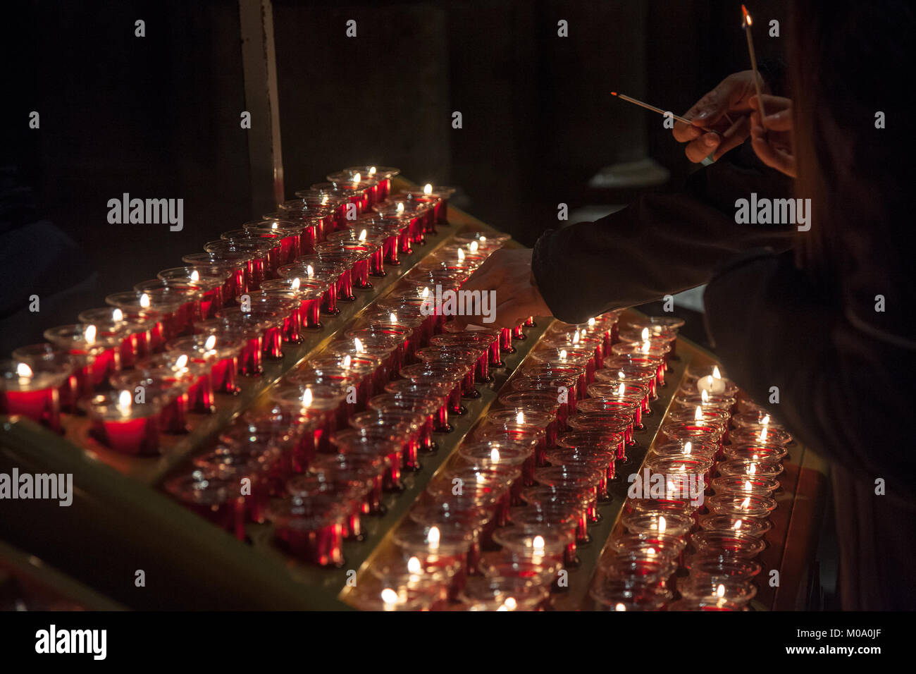 People lighting candles in the Notre Dame cathedral in Paris, France. Burning a candle is a usual practice in Catholicism - Stock Image