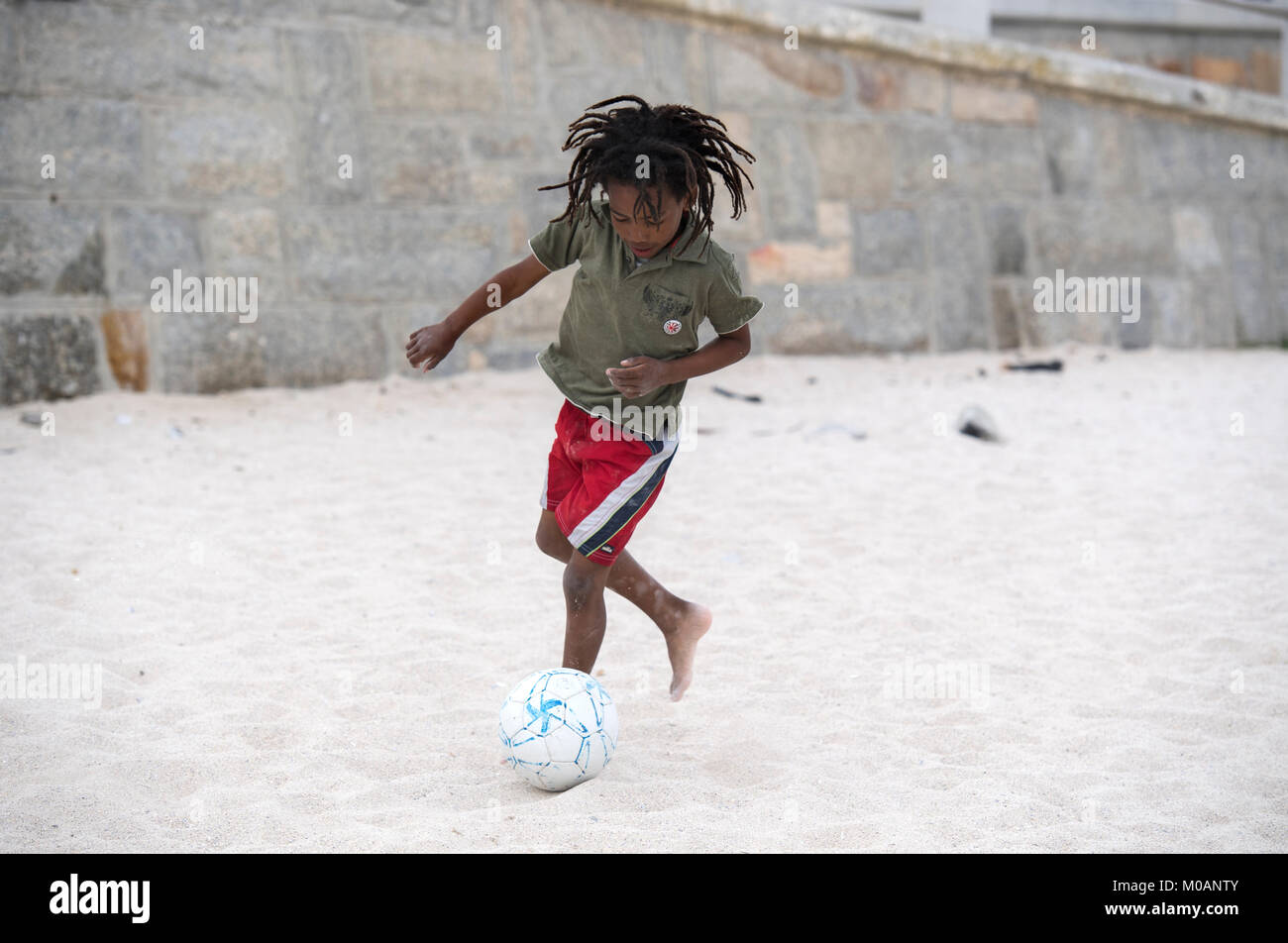 Young boy playing football on a sandy beach in Cape Town, South Africa - Stock Image