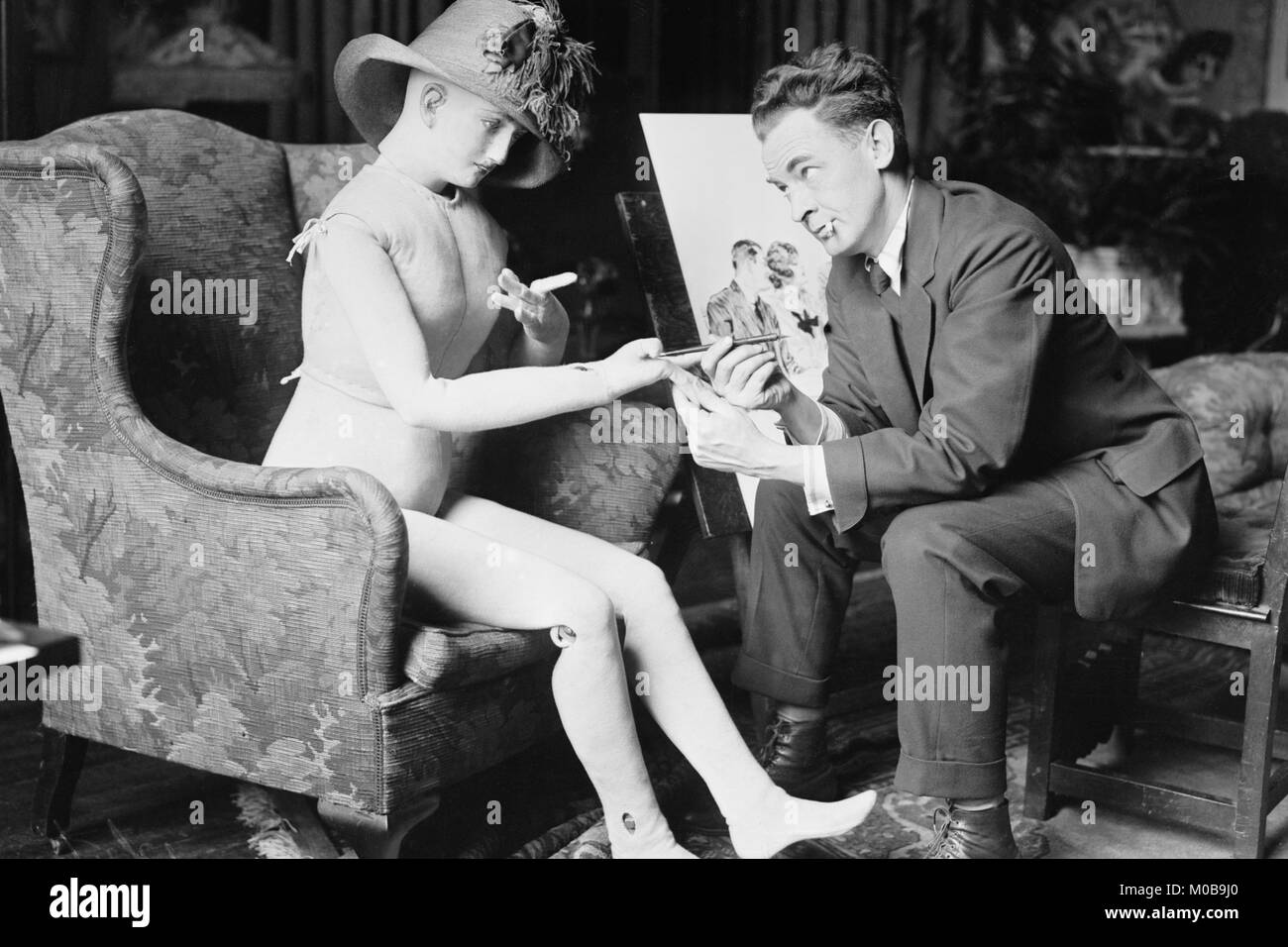 James Montgomery Flagg Poses with a Girl Manikin that he uses from which to paint - Stock Image