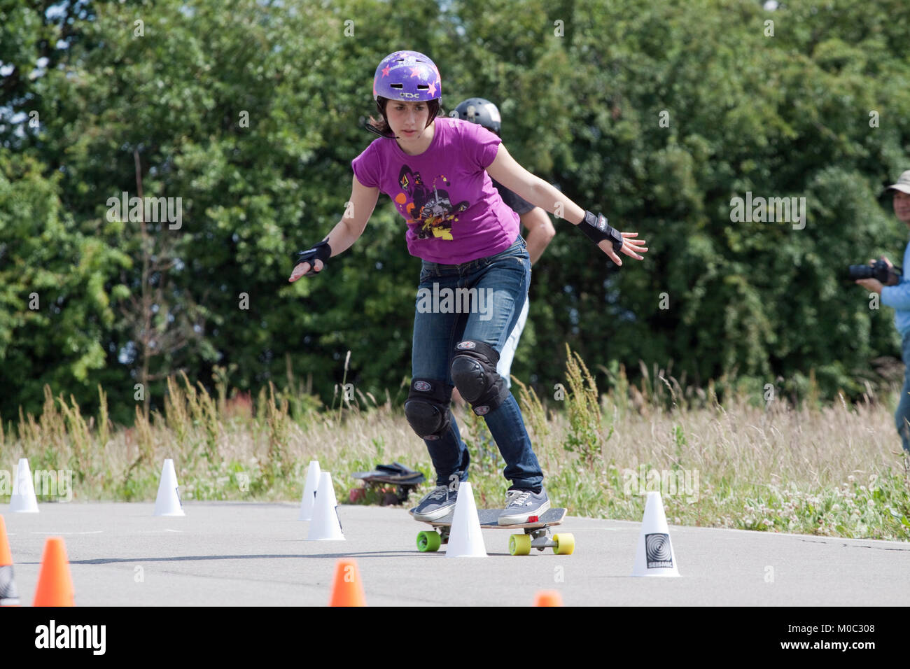 Woman skateboarder competing in a slalom - Stock Image