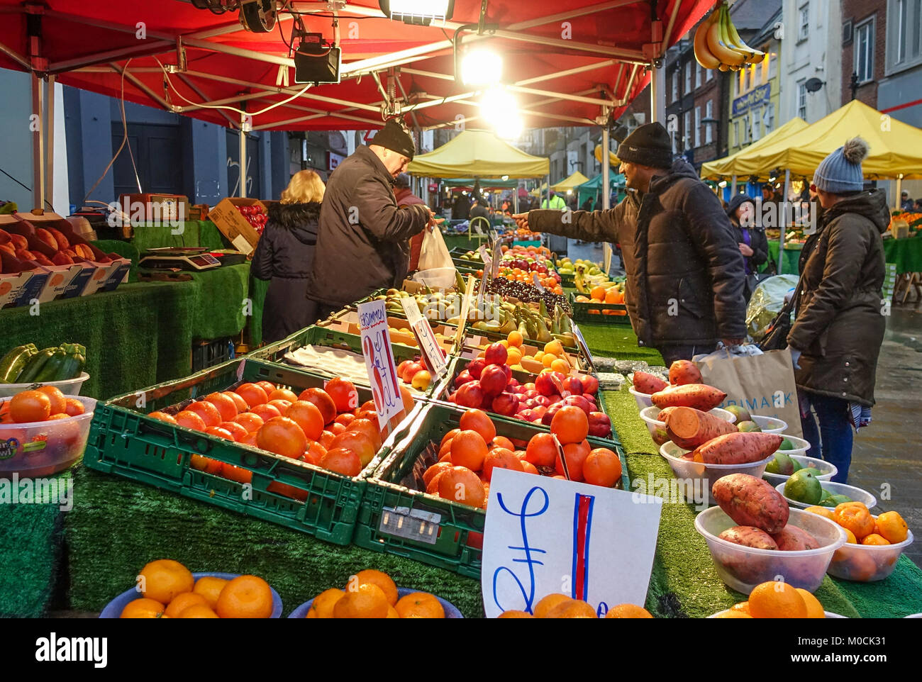 a-market-stall-vendor-on-a-fruit-and-veg-stall-makes-a-sale-at-surrey-M0CK31.jpg