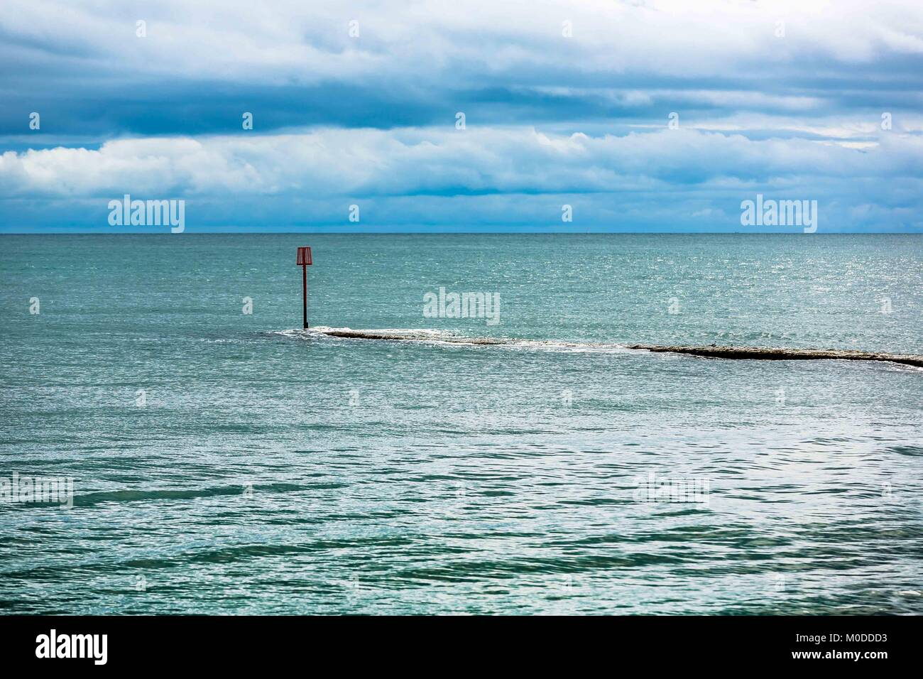 A concrete jetty stretching out to sea n the South Devon coast of England. - Stock Image