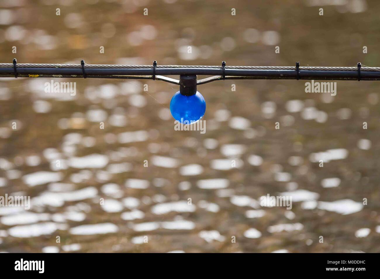 Single electric light bulb hanging over a stream or river. - Stock Image