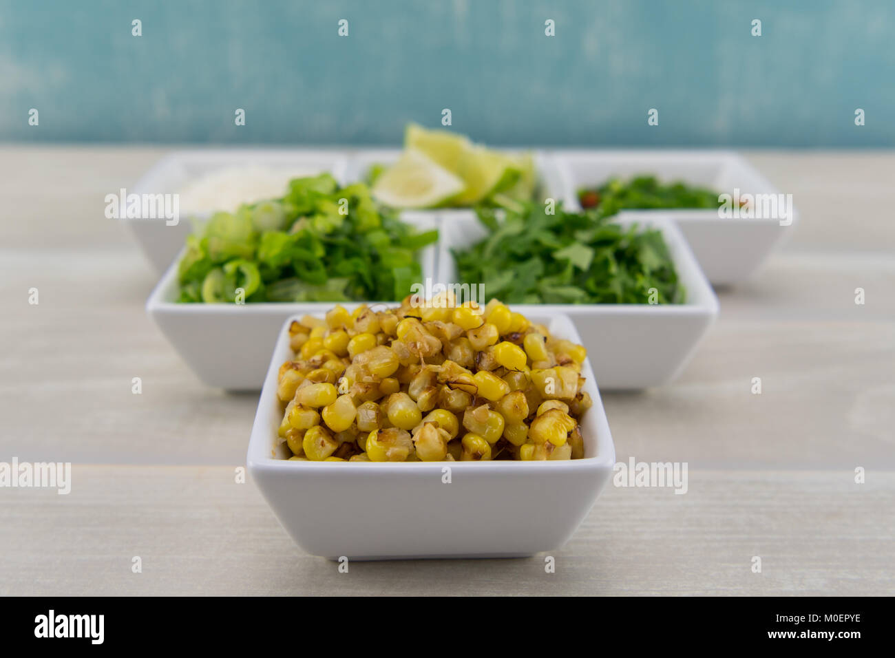 Roasted Corn in White Bowl in front of other seasonings - Stock Image