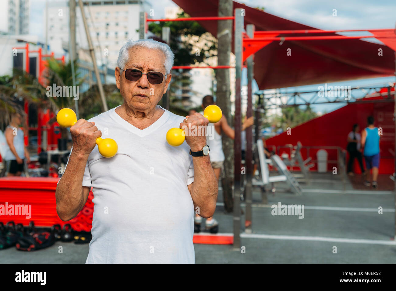 Model Released: Older man (80-89) exercising using dumbbells at public gym in Ipanema, Rio de Janeiro, Brazil Stock Photo