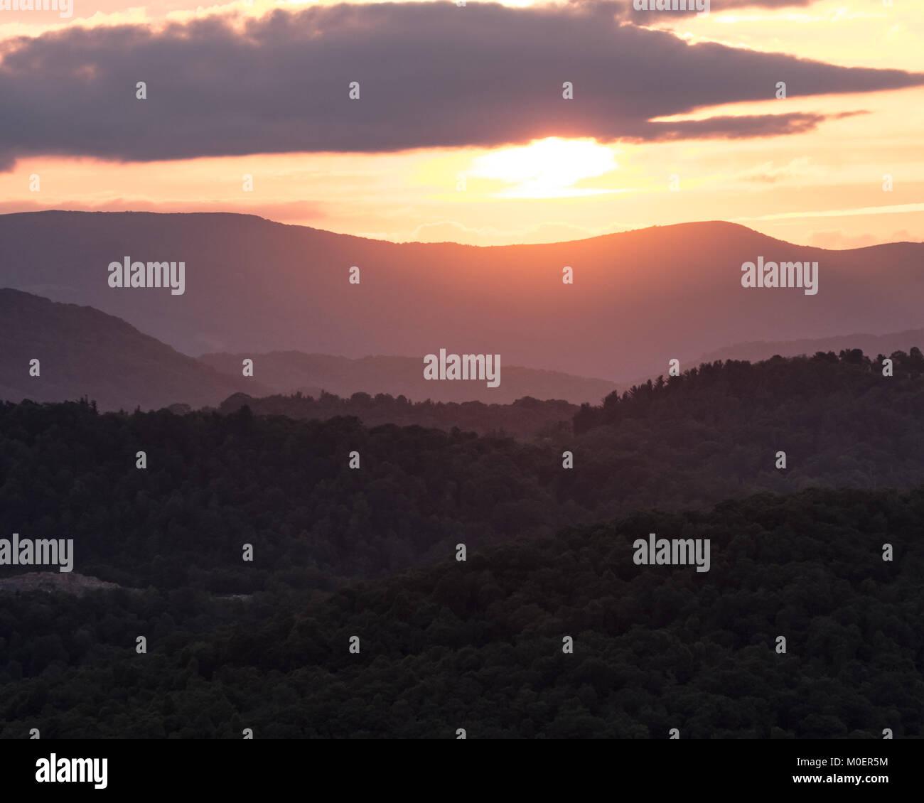 Sun Begins to Set Below Blue Ridge Mountain Ridges - Stock Image