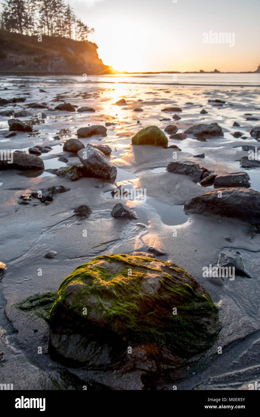 Sun set glows over rocks at low tide on Oregon beach - Stock Image