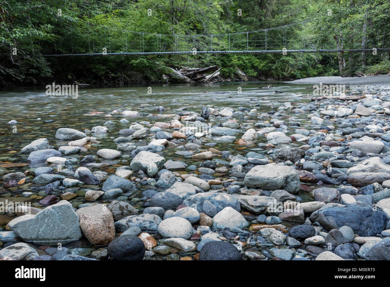 Suspension Bridge Over Rocky Creek in the Cascade mountains - Stock Image