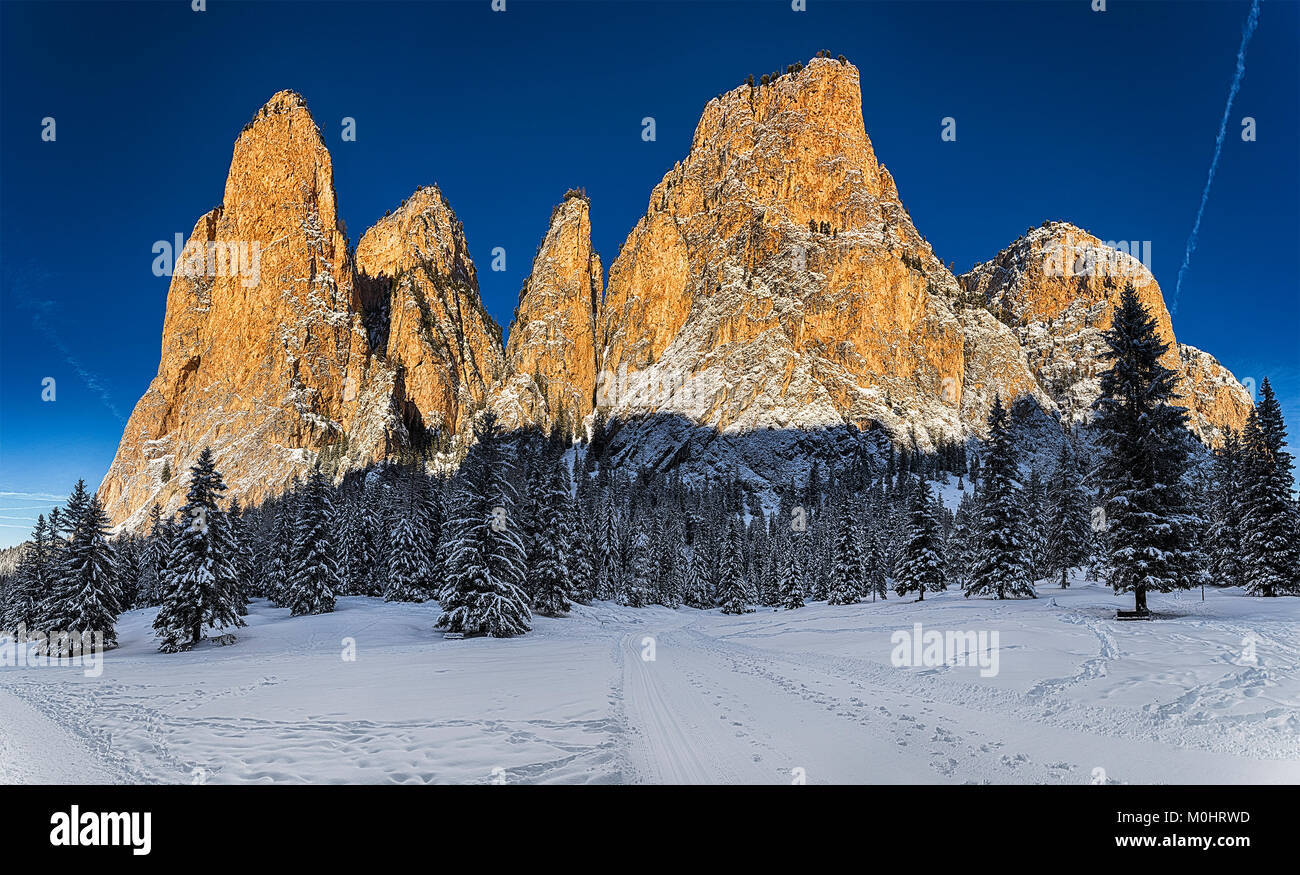 Rays of Sun on the mountains of Gardena Valley in a beautiful winter morning with blue sky in background - Stock Image