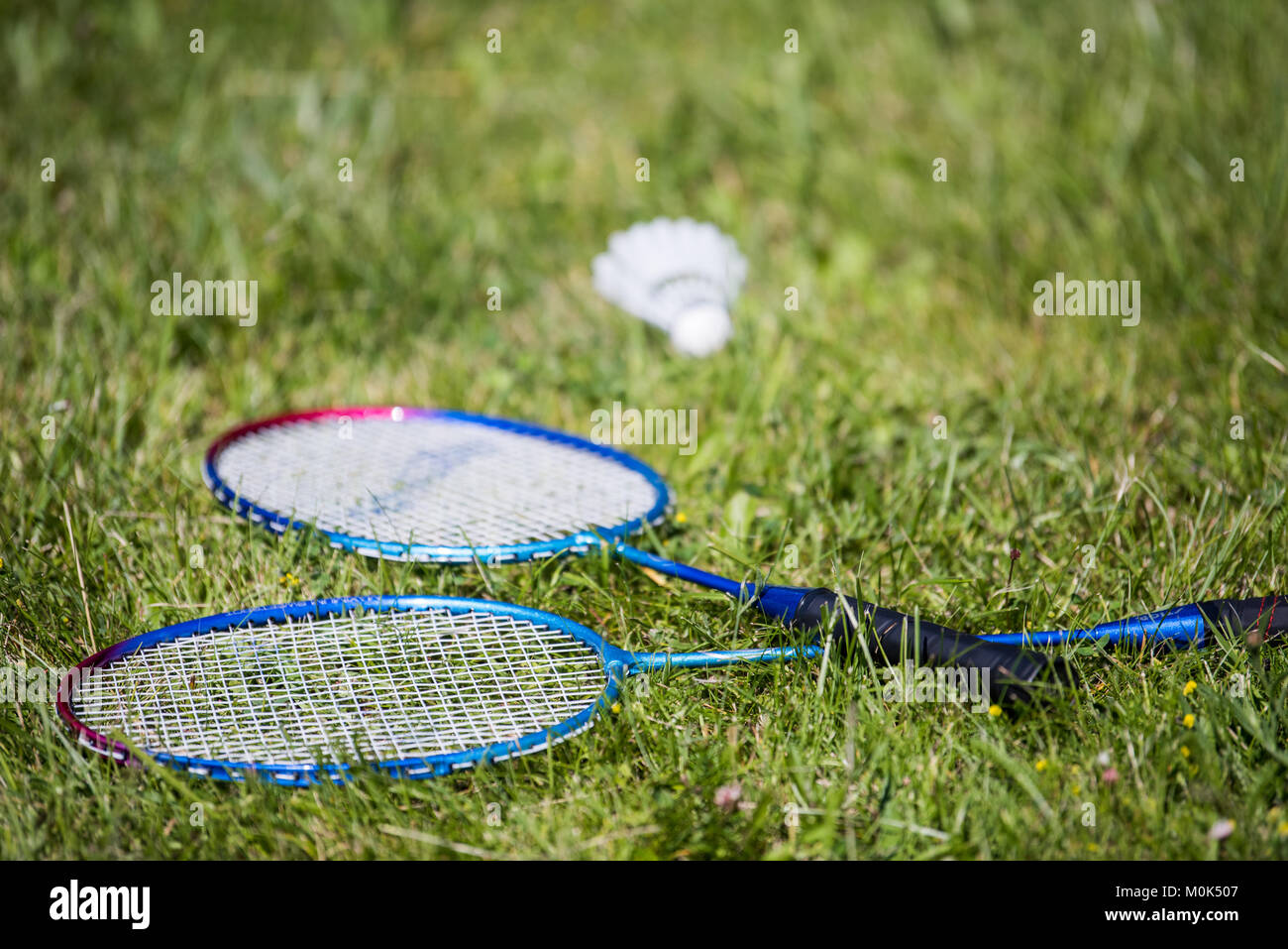 Exercise break during a summer vacation badminton game - Stock Image