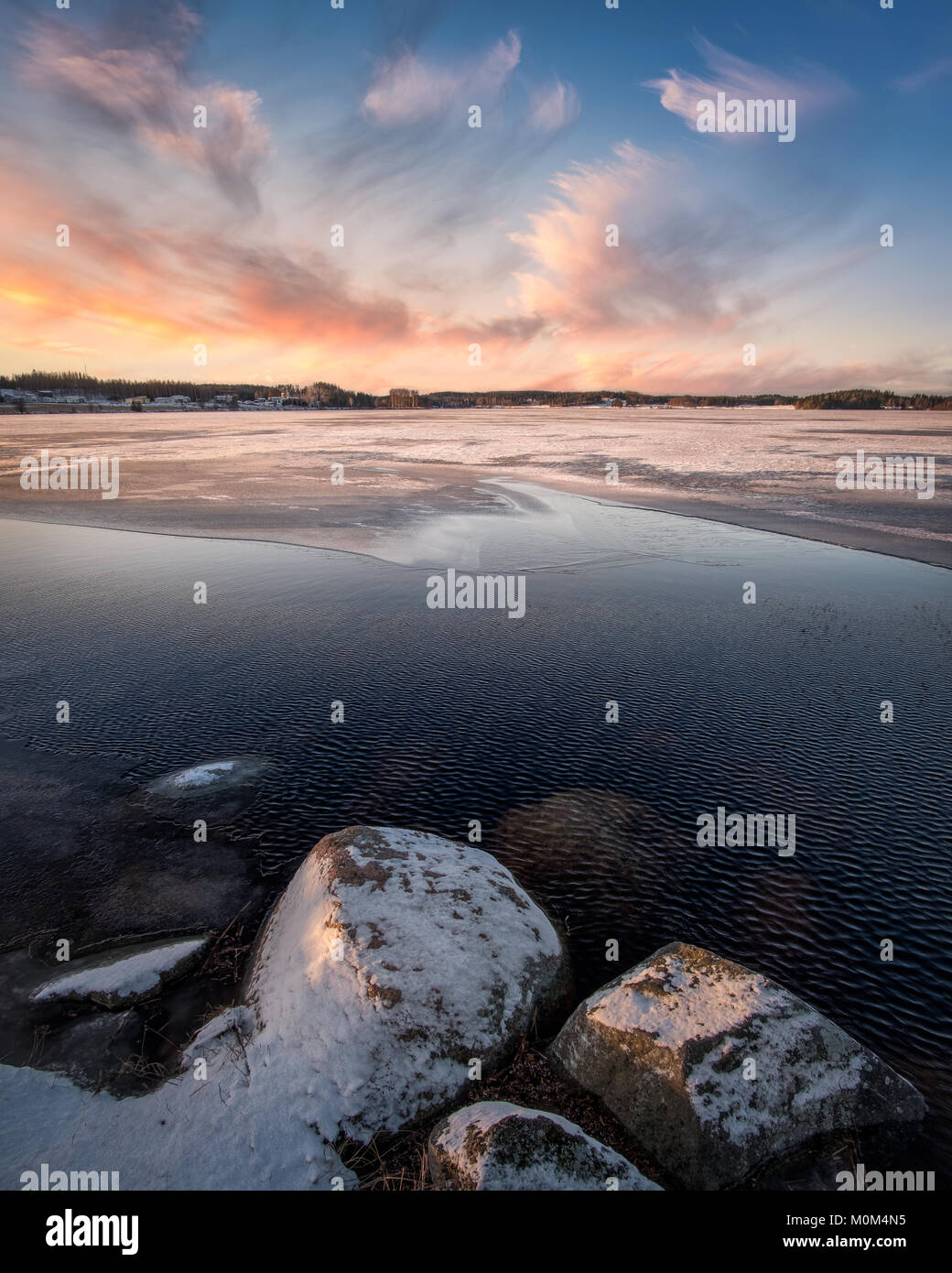 Scenic landscape with sunset and freezing lake at winter evening in FInland - Stock Image