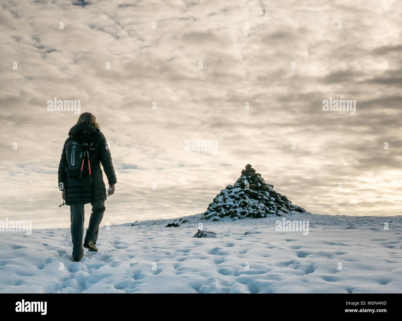 woman-walking-in-snow-uphill-on-footpath