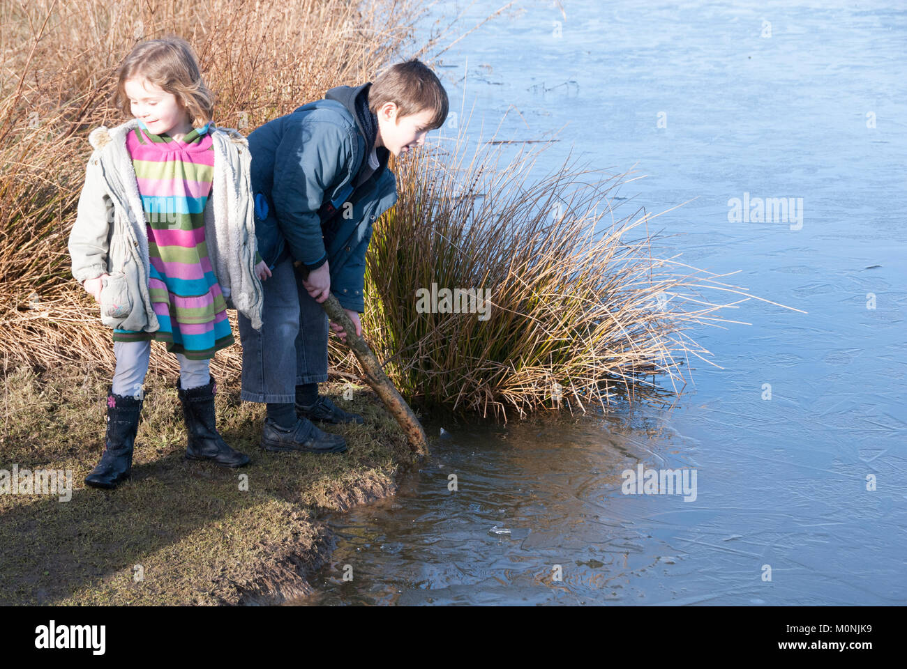 Sheffield, UK- 08 Feb: Children play, smashing the ice on the frozen lake on 08 Feb 2015 at Rother Valley Country - Stock Image