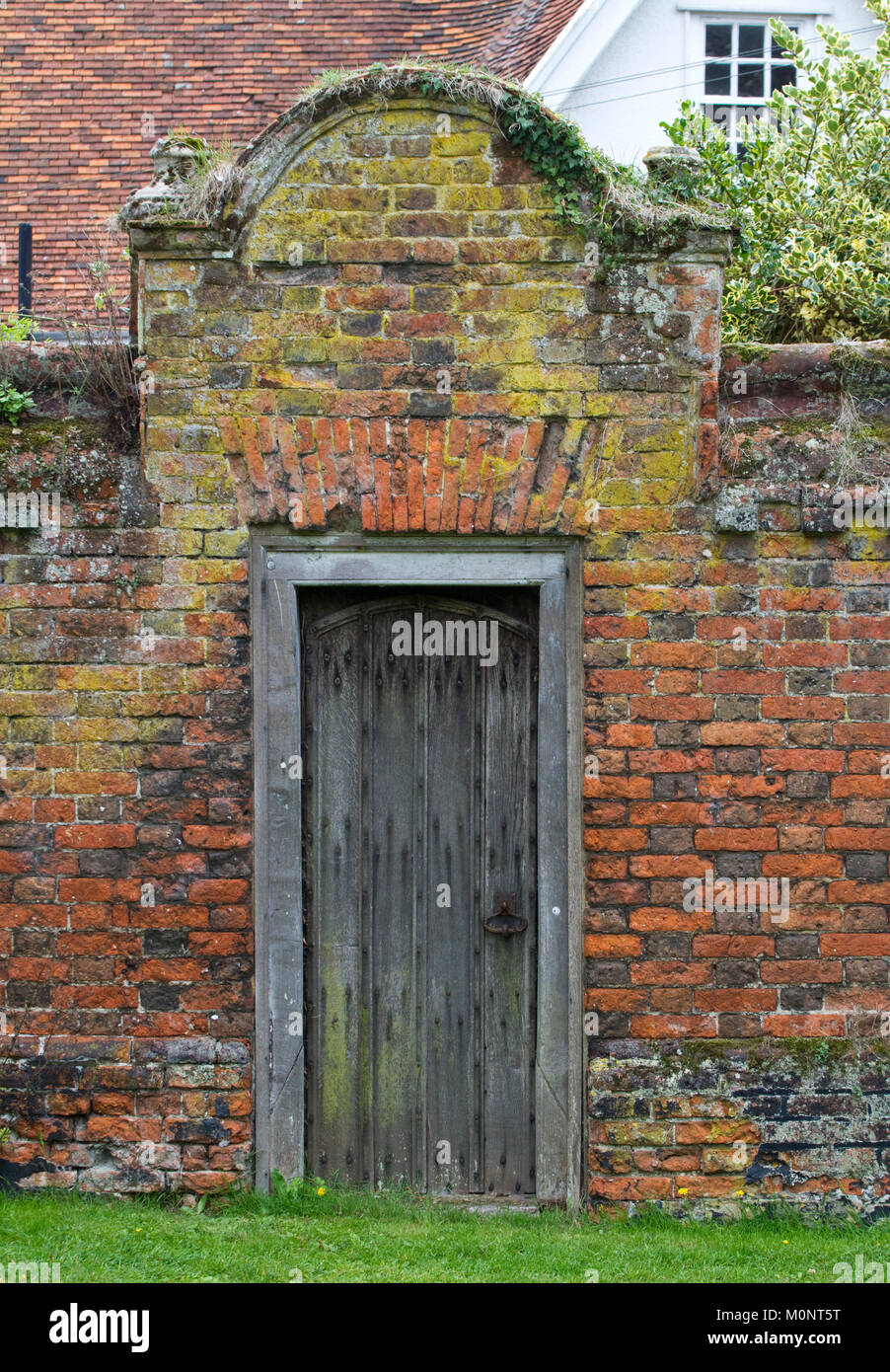 Period wooden door in a red brick garden wall - Stock Image