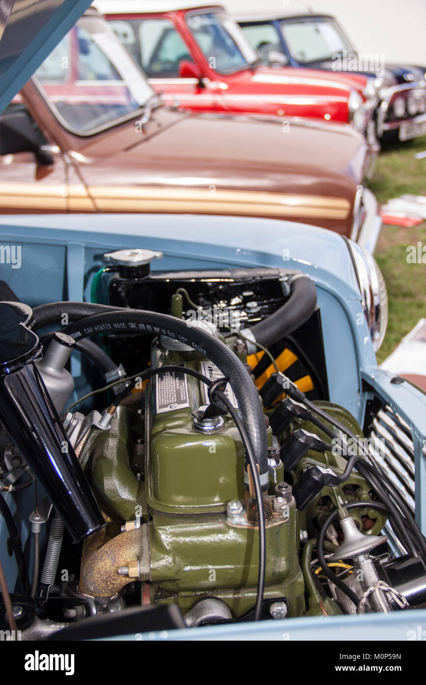 BMC A series engine of an old Austin mini, with other minis behind. - Stock Image