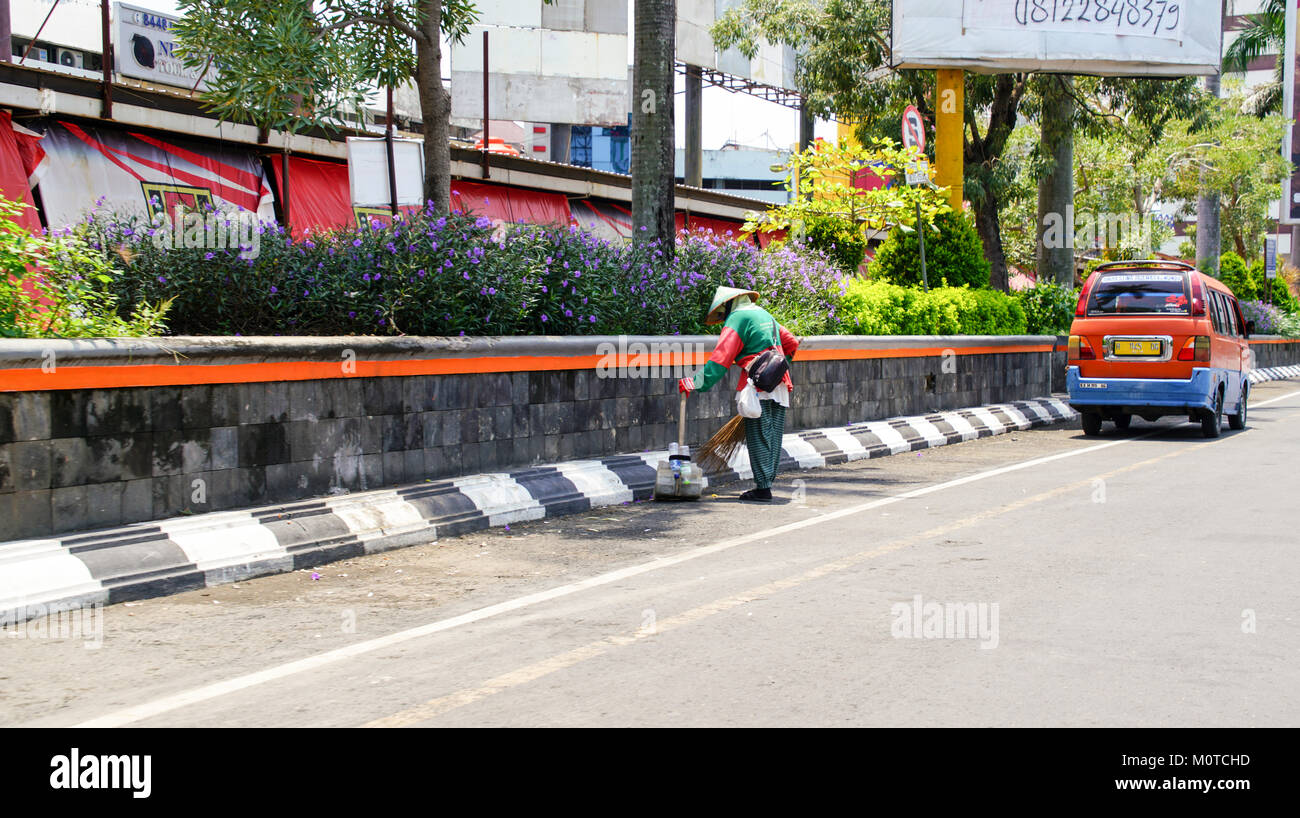 A worker cleans up trash from the street. Samarang, Java, Indonesia - Stock Image