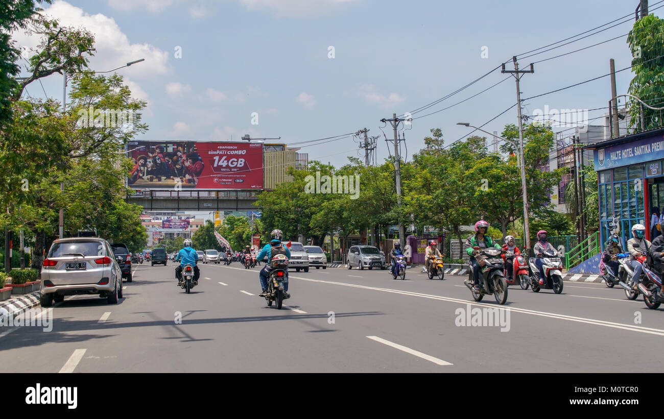 Mid-day traffic on one of the major streets in Semarang, Indonesia. There are far more motorcycles and scooters - Stock Image
