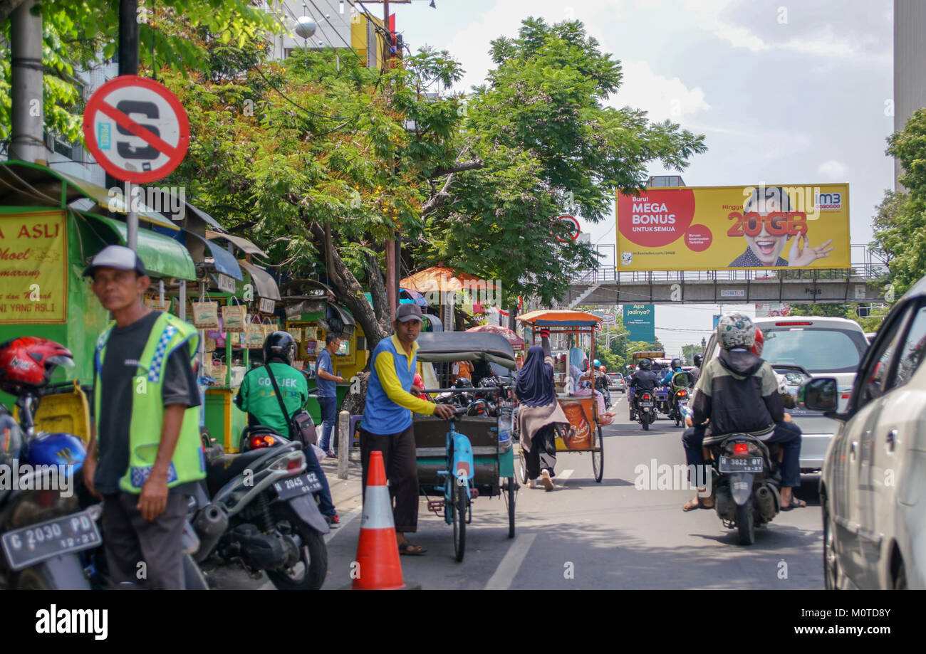 A row of foodcarts line the side of this major street in Semarang, Indonesia - Stock Image