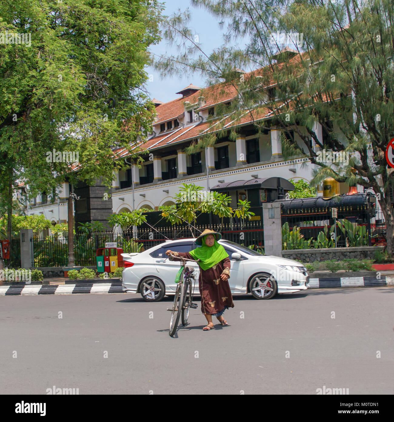 An older Javanese woman walks her bicycle across the street. Semarang, Java, Indonesia. The Railway Building is - Stock Image