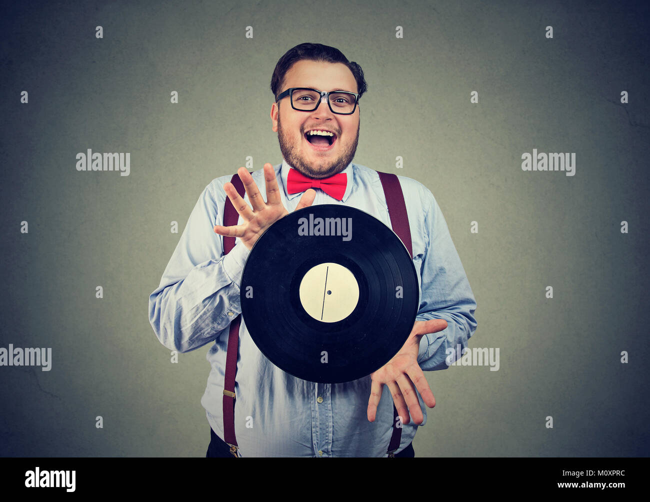 Chubby happy man in bow-tie happy with vinyl record obsessed with music. - Stock Image